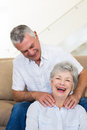 Man giving his senior wife a shoulder rub who is smiling at camera home in living room Royalty Free Stock Photography