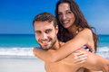 Man giving piggy back to his girlfriend at the beach on a sunny day Royalty Free Stock Images