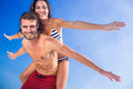 Man giving piggy back to his girlfriend at the beach on a sunny day Royalty Free Stock Photo
