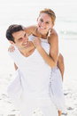 Man giving a piggy back to woman on the beach women sunny day Royalty Free Stock Images
