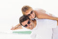 Man giving a piggy back to woman on the beach women sunny day Royalty Free Stock Photo