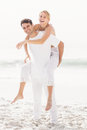Man giving a piggy back to woman on the beach women sunny day Royalty Free Stock Photos