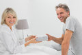 Man giving present to his smiling partner looking at camera home in bedroom Royalty Free Stock Images