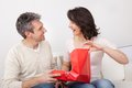 Man giving a present to woman mature men his women at home Stock Photo