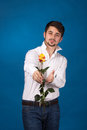Man giving the red roses on blue background Royalty Free Stock Photos