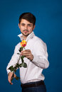 Man giving the red roses on blue background Stock Photography