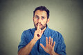 Man giving shhhh quiet silence secret gesture on gray wall background young handsome Stock Images