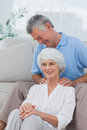 Man giving a shoulder massage to his wife at home on the couch Royalty Free Stock Photography