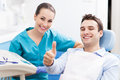 Man giving thumbs up at dentist office young men Stock Images