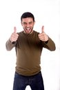 Man giving thumbs up smiling the double hand gesture wearing a brown shirt on a white background Stock Photo
