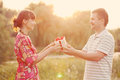 Man giving to his woman a gift box retro style women happy middle aged couple in love outdoors in the sunlight at sunset happy Royalty Free Stock Image