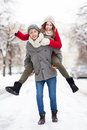 Man giving woman piggyback in winter setting Royalty Free Stock Images
