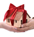 Man giving wooden house model tied with a bow to woman Royalty Free Stock Photo