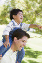 Man giving young boy shoulder ride smiling Royalty Free Stock Photos