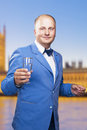 Man with glass standing against the palace of westminster portrait vertical shot Stock Photos