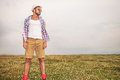 Man with glasses and hat standing in a field casual young looks away to his side Royalty Free Stock Images