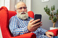 Man in glasses sitting on the chair with smartphone Royalty Free Stock Photo