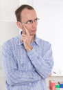 Man with glasses touching chin and skeptical at office in shirt Royalty Free Stock Photo