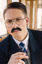 Man with glasses and whiskers in a suit sitting in an old woode photo of wooden wagon train smoking cigar retro vintage fashion Stock Photography