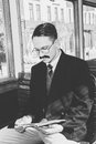 Man with glasses and whiskers in suit sitting in an old wooden black white photo of wagon train smoking cigar while Stock Photo