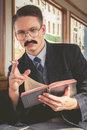 Man with glasses and whiskers in suit sitting in an old wooden photo of wagon train smoking cigar while reading book retro Stock Images