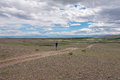 A man goes along a dirt road in the steppe landscape with clouds sky and mountains on horizon Royalty Free Stock Photography
