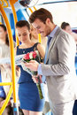 Man going to date on bus holding bunch of flowers and mobile phone text messaging Stock Photo
