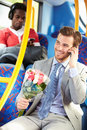 Man going to date on bus holding bunch of flowers whilst mobile phone talking Stock Images