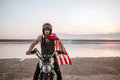Man in golden helmet and american flag cape driving motorcycle Royalty Free Stock Photo