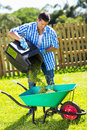 Man grass wheelbarrow young emptying lawnmower into a after mowing Royalty Free Stock Photo