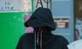 Man in gray cowl hiding his face
