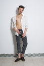 A man in a gray jeans and white cardigan on naked body the studio Stock Image