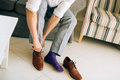The man in gray slacks and a purple dress socks brown shoes with
