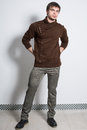 The man in gray trousers and fashionable brown sweater studio Stock Image