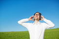 Man in a green field enjoying his music listening to on earphones standing with head tilted back to the sun and blissful Stock Images