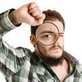 Man in green shirt looking through a magnifying glass. Royalty Free Stock Image