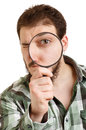 Man in green shirt looking through a magnifying glass. Royalty Free Stock Photos