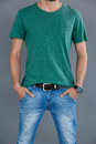 Man in green t-shirt posing with hands in pockets Royalty Free Stock Photo