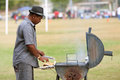Man Grills Hamburgers For Youth Football Game Stock Image