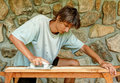 Man grinding wooden plank young so he can use it for his new floor Royalty Free Stock Photo