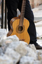 Man with guitar acoustic against a stone background Stock Images