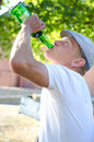 Man gulping alcohol from a bottle with drinking addiction as he sits outdoors in the garden under the shade of tree Royalty Free Stock Images
