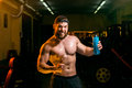 Man in the gym with shaker drinking from Stock Images