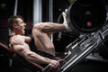 Man in gym training at leg press to define his upper muscles Royalty Free Stock Images