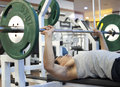 Man gym workout using a squat machine at fitness club Stock Photo