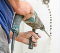 Man with hammer drill doing hole for socket Royalty Free Stock Image