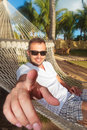 Man in a hammock in a resort pointing his finger Royalty Free Stock Photos