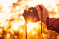 Man hand holding retro photo camera outdoor hipster lifestyle with sun lights bokeh autumn nature on background Royalty Free Stock Photography