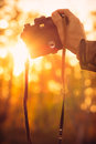 Man hand holding retro photo camera outdoor hipster lifestyle with sun lights bokeh autumn nature on background Stock Photography
