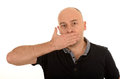 Man with hand over mouth bald middle aged speak no evil concept isolated on white background Stock Photos